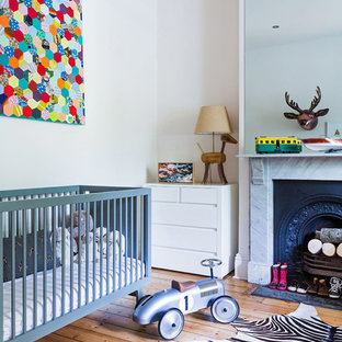Photo of an eclectic nursery for boys in Melbourne with beige walls and light hardwood floors.