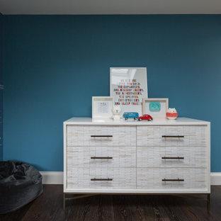 Réalisation d'une chambre de bébé vintage de taille moyenne avec un mur bleu, un sol en bois foncé et un sol marron.