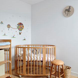 Design ideas for a small contemporary gender-neutral nursery in Melbourne with white walls, light hardwood floors and beige floor.