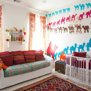 Mediterranean gender neutral nursery in Houston with multi-coloured walls and painted wood flooring.