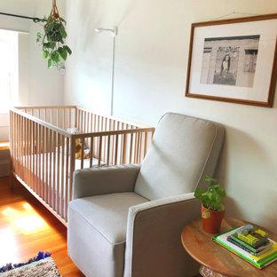 Idées déco pour une petit chambre de bébé fille éclectique avec un mur blanc, un sol en bois brun, un sol marron et un plafond en lambris de bois.