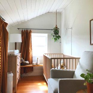 Immagine di una piccola cameretta per neonata boho chic con pareti bianche, pavimento in legno massello medio, pavimento marrone e soffitto in perlinato