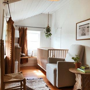 Foto de habitación de bebé niña bohemia, pequeña, con paredes blancas, suelo de madera en tonos medios y suelo marrón