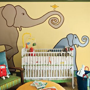 Photo of a bohemian gender neutral nursery in Atlanta with yellow walls and dark hardwood flooring.