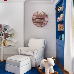 This is an example of a bohemian gender neutral nursery in Boston with white walls, medium hardwood flooring and blue floors.