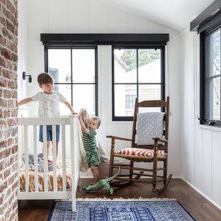 Modelo de habitación de bebé neutra mediterránea con paredes blancas, suelo de madera en tonos medios y suelo marrón