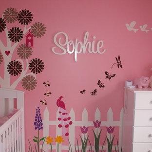 Immagine di un'ampia cameretta per neonata minimal con pareti rosa