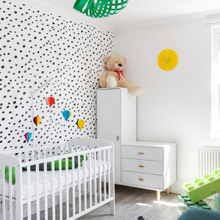 This is an example of a medium sized scandi gender neutral nursery in London with multi-coloured walls, light hardwood flooring, grey floors and wallpapered walls.