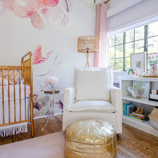 Inspiration for a large classic nursery for girls in New York with white walls, medium hardwood flooring and brown floors.