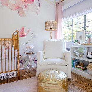 Ejemplo de habitación de bebé niña tradicional renovada, grande, con paredes blancas, suelo de madera en tonos medios y suelo marrón