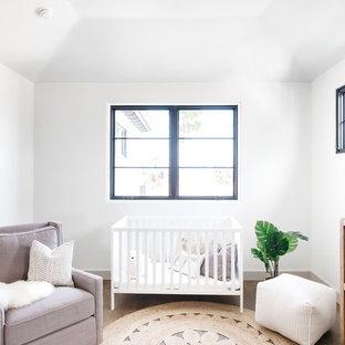 Modelo de habitación de bebé neutra mediterránea con paredes blancas, suelo de madera oscura y suelo marrón