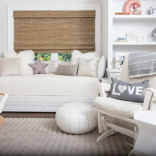 Diseño de habitación de bebé neutra clásica renovada con paredes beige, suelo de madera en tonos medios y suelo gris