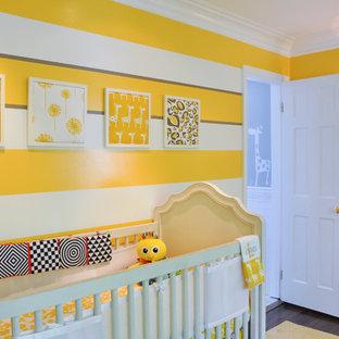 Réalisation d'une chambre de bébé neutre tradition avec un mur jaune et un sol en bois foncé.