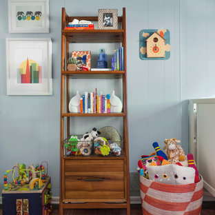 Diseño de habitación de bebé neutra bohemia, de tamaño medio, con paredes azules, suelo rojo y moqueta