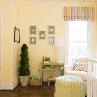 Modelo de habitación de bebé neutra tradicional renovada con paredes amarillas y suelo de madera oscura