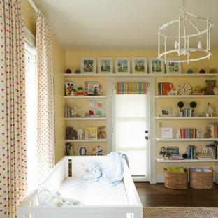 Réalisation d'une grand chambre de bébé neutre tradition avec un mur jaune et un sol en bois foncé.