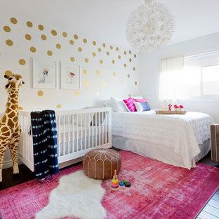 На фото: маленькая комната для малыша в стиле фьюжн с белыми стенами, полом из ламината и коричневым полом для девочки с
