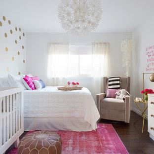 Modelo de habitación de bebé niña ecléctica, pequeña, con paredes blancas, suelo laminado y suelo marrón