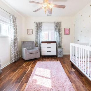This is an example of a large modern nursery for girls in Indianapolis with white walls, medium hardwood flooring and brown floors.