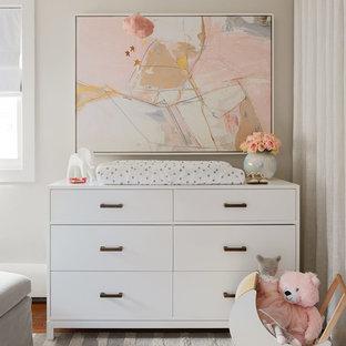 Cette photo montre une chambre de bébé fille tendance de taille moyenne avec un mur gris, un sol en bois foncé et un sol gris.