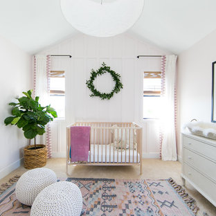 This is an example of a nautical nursery for girls in Orange County with pink walls, carpet and beige floors.