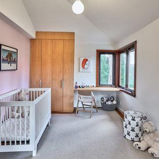 Imagen de habitación de bebé retro, de tamaño medio, con paredes rosas y suelo de corcho