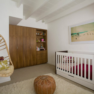 Inspiration for a mid-sized modern girl carpeted nursery remodel in San Diego with white walls