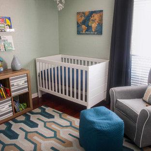 Modelo de habitación de bebé niño minimalista, pequeña, con paredes verdes, suelo de madera oscura y suelo marrón
