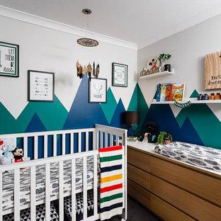 Imagen de habitación de bebé niño clásica renovada, pequeña, con paredes azules y moqueta