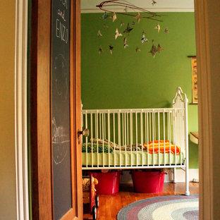 Bohemian nursery for boys in Albuquerque with green walls and medium hardwood flooring.