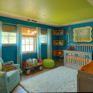 Design ideas for a medium sized classic gender neutral nursery in Vancouver with blue walls and medium hardwood flooring.