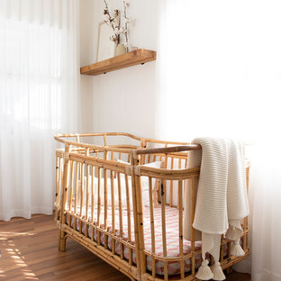 Photo of a beach style nursery for girls in Gold Coast - Tweed with beige walls and medium hardwood floors.