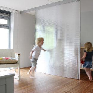 Modelo de habitación de bebé neutra actual con paredes blancas y suelo de madera en tonos medios
