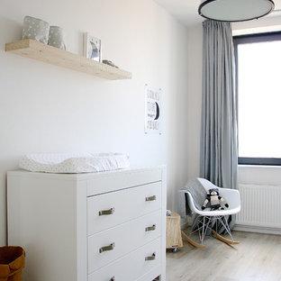 Imagen de habitación de bebé neutra escandinava con paredes blancas, suelo de madera clara y suelo beige