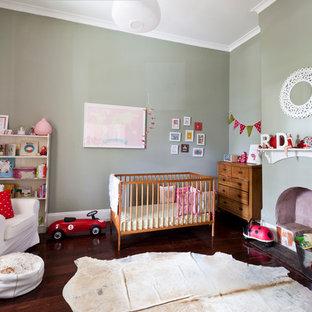 Modelo de habitación de bebé neutra bohemia, grande, con paredes grises, suelo de madera oscura y suelo marrón