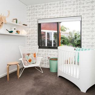 Modelo de habitación de bebé neutra actual, pequeña, con paredes multicolor, moqueta y suelo marrón