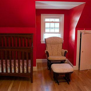 Imagen de habitación de bebé neutra tradicional renovada, de tamaño medio, con paredes rojas y suelo de madera en tonos medios