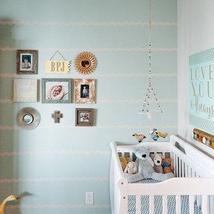 Diseño de habitación de bebé neutra clásica renovada con paredes verdes, suelo de madera oscura y suelo marrón