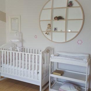 Cette image montre une chambre de bébé fille traditionnelle de taille moyenne avec un mur beige et un sol en linoléum.