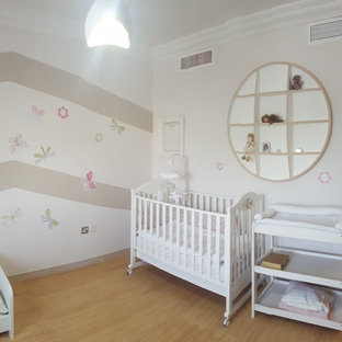 Foto de habitación de bebé niña clásica renovada, de tamaño medio, con paredes beige y suelo de linóleo