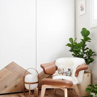 Diseño de habitación de bebé contemporánea con suelo de madera clara