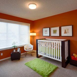 Cette photo montre une chambre de bébé neutre tendance de taille moyenne avec un mur orange et moquette.