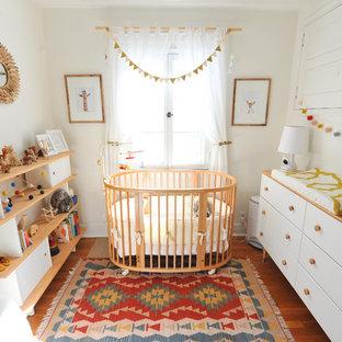 Idee per una cameretta per neonati neutra scandinava con pareti bianche, pavimento arancione e pavimento in legno massello medio