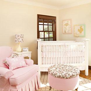 Inspiration pour une chambre de bébé fille traditionnelle avec un mur beige et un sol en bois brun.