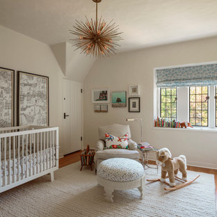 Inspiration for a timeless medium tone wood floor and beige floor nursery remodel in Portland with white walls
