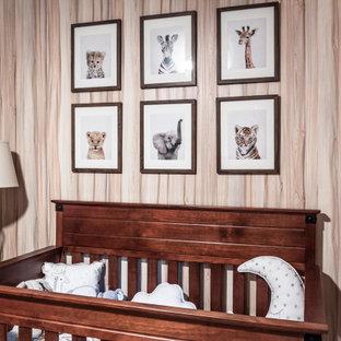 Immagine di una piccola cameretta per neonati neutra chic con pareti verdi, pavimento in bambù, pavimento beige e carta da parati