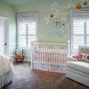 Esempio di una grande cameretta per neonata classica con pareti verdi e moquette