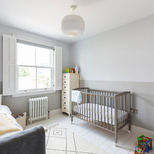 This is an example of a classic gender neutral nursery in London with grey walls, painted wood flooring and white floors.