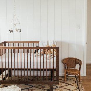 Diseño de habitación de bebé neutra clásica renovada con paredes blancas, suelo de madera en tonos medios y suelo marrón