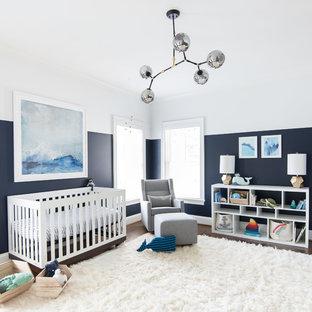 Modelo de habitación de bebé neutra tradicional renovada con paredes azules, suelo de madera oscura y suelo blanco